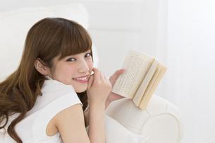 ソファーの上で本を持ち笑う女性 FYI00465862