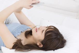 ベッドの上でスマートフォンを持ち笑う女性 FYI00465865