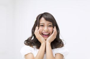 頬に両手を当て笑う女性 FYI00465956