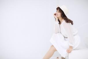 帽子を被り座って微笑む女性 FYI00465962