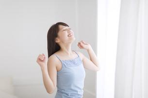 窓際で腕を上げ伸びをする女性 FYI00467171