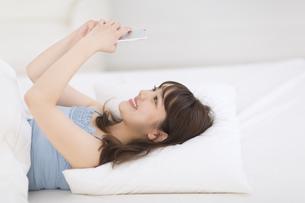 ベッドでスマートフォンを見る女性 FYI00467172
