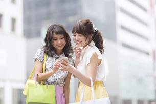 街中でスマートフォンを見る女性2人 FYI00467191