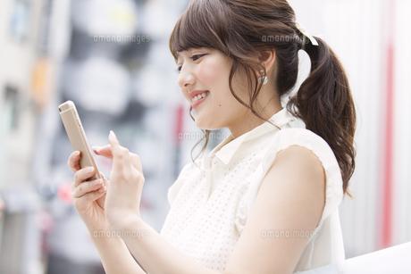 街中でスマートフォンを見る女性 FYI00467193