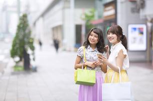 街中でスマートフォンを持ち微笑む女性2人 FYI00467210
