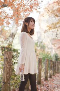 秋の紅葉した公園で立ってペットボトルを持っている女性 FYI00467257