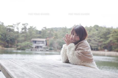 公園のテーブルに肘を付くニットセーターを着た女性 FYI00467271