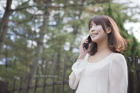 建物の前で電話をする女性 FYI00467279