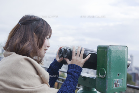 展望台から双眼鏡で神戸の景色を望む笑顔の女性 FYI00467300