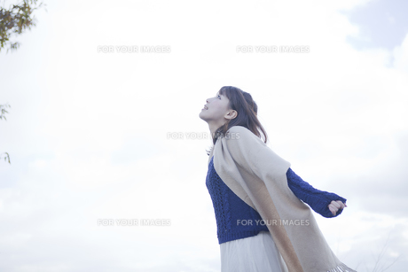 高台で伸びをするストールを巻いた女性 FYI00467304