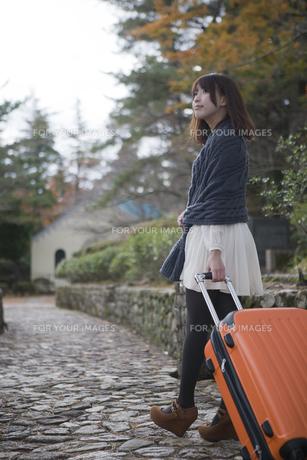 秋の石畳をトランクを引いて歩く笑顔の女性 FYI00467308