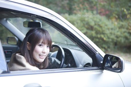 秋の紅葉の公園の駐車場で車の運転をする女性 FYI00467320
