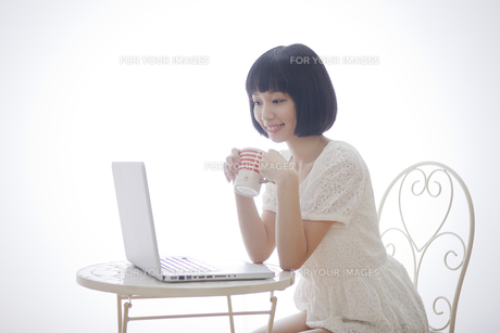 テーブルでコップを持ちながらパソコンを見る女性 FYI00467478