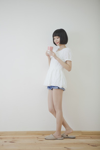 コップを持って立っている女性の素材 [FYI00467525]