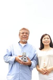 クラシックカメラを持って佇むシニア夫婦 FYI00469676