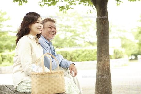 公園のベンチに座っているシニア夫婦 FYI00469739