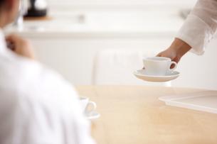 コーヒーをテーブルに置く日本人女性の手元 FYI00470279