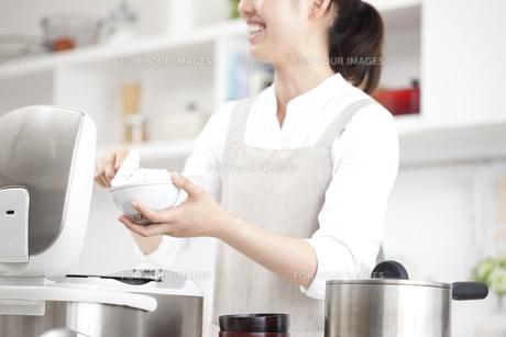 米を茶碗によそう女性 FYI00470353
