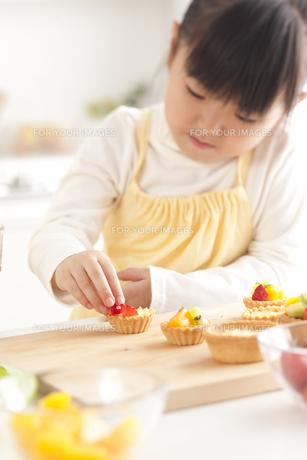 キッチンでフルーツタルトを作る女の子 FYI00470370