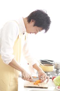 キッチンで野菜を切る若い男性 FYI00470380
