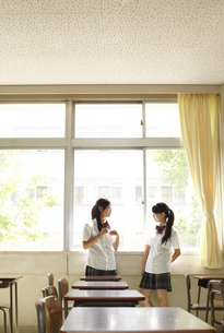 教室の窓際に立って話をしている女子高生二人 FYI00471311