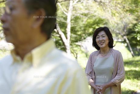 緑の中で夫の後ろ姿を笑顔で見ている妻 FYI00471335