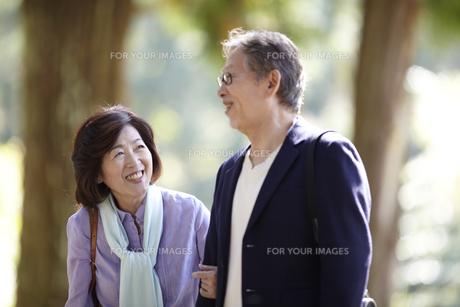 腕を組み笑顔で歩くシニア夫婦 FYI00471338