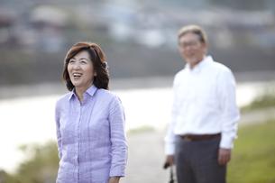 川岸の歩道で笑顔の妻の後姿を見ているシニア男性 FYI00471345