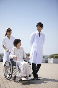 青空と車椅子の笑顔のシニア女性と女性看護師と医師 FYI00471589