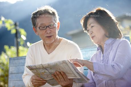 田舎町の駅のホームのベンチに座り地図を見ているシニア夫婦 FYI00471679
