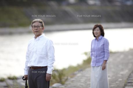 川岸の石畳の歩道で夫の後姿を見るシニア女性 FYI00471688