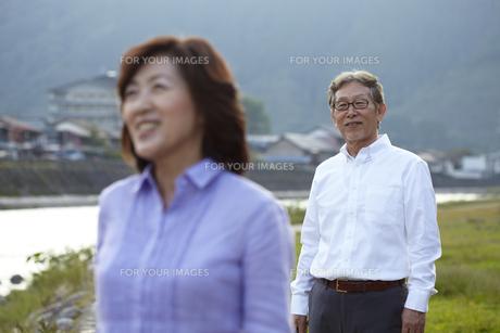 川岸の歩道で笑顔の妻の後姿を優しい目で見ているシニア男性 FYI00471692