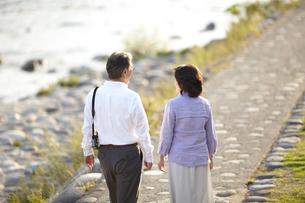 夕暮れの川岸の石畳の歩道を歩くシニア夫婦の後姿 FYI00471704