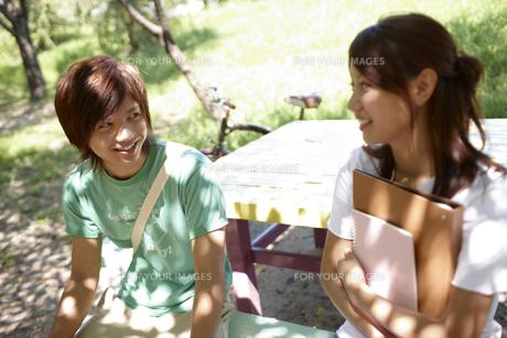 大学のキャンパスの木陰のベンチで話をする男女の大学生 FYI00471747