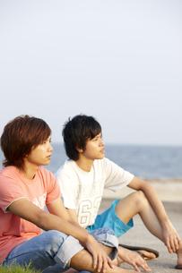 海辺に座り夕日を見ている若者二人 FYI00471748