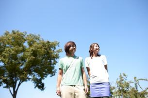 青空を背景に遠くを見つめる笑顔の若い男女のポートレート FYI00471759