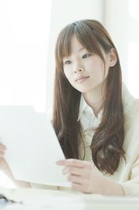 書類を見つめる若い日本人女性 FYI00474026