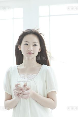 コップを持ち髪をなびかせる若い日本人女性 FYI00474037