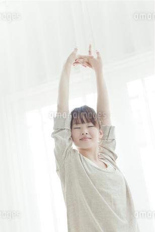 室内で背伸びをする若い日本人女性 FYI00474057
