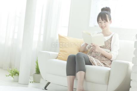 ソファーで本を読む若い日本人女性 FYI00474061