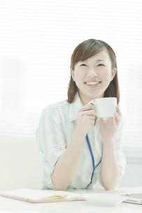 コーヒーを飲む笑顔のビジネスウーマン FYI00474097