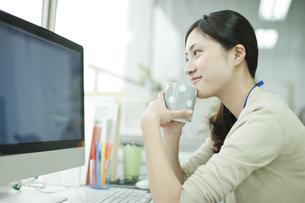コーヒーを飲みながらパソコンを閲覧するビジネスウーマン FYI00474119