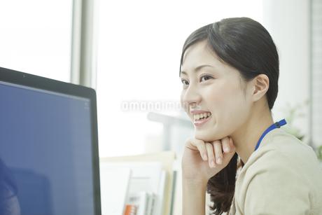パソコンの前で頬杖をする笑顔のビジネスウーマン FYI00474131