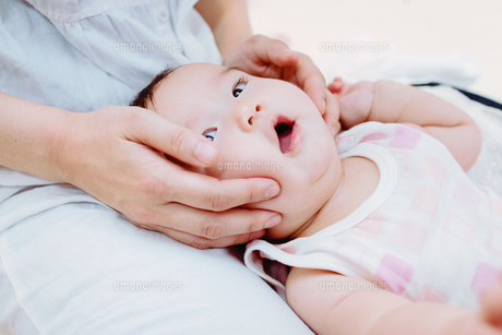 お母さんにほっぺを挟まれる赤ちゃん FYI00481488