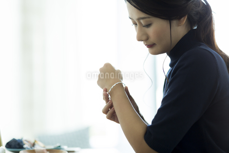 アクセサリーを着ける女性 FYI00482008