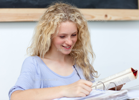 Portrait of a  cute teen girl studying FYI00482084