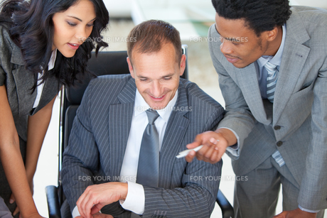Manager with employees working in office FYI00482112