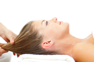 Relaxed woman enjoying a hair massage FYI00482540