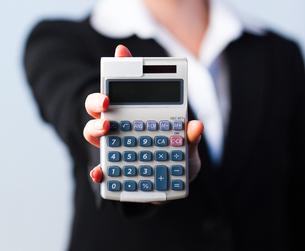 Business woman holding calculator FYI00482655