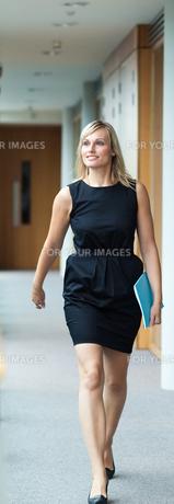 Confident businesswoman walking through a corridorの素材 [FYI00482676]